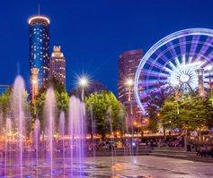 Imagen de una fuente y rueda de la fortuna en Atlanta, GA, de noche